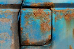 Close up of a rusted blue vintage car fuel tank cover. Rusted petrol cap cover. Rusted metal background. Rusty metal texture
