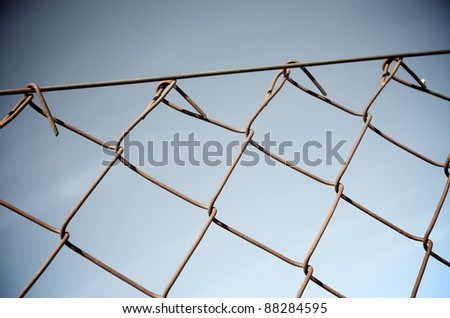Close up of a rusty metal fence with a blue background