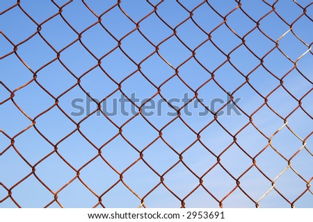 Close up of a rusty metal security fence.