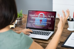 Close-up Of A Sad Businesswoman With Laptop Screen Showing Personal Files Encrypted Text