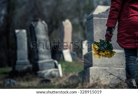 Close-up of a Sad Woman Holding Sunflowers in front of a Loved one\'s Gravestone. Focus on the Bouquet.