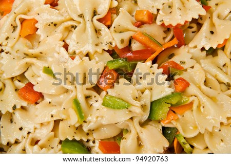 Close up of a salad with bow tie pasta, green and red bell peppers and Italian seasonings.