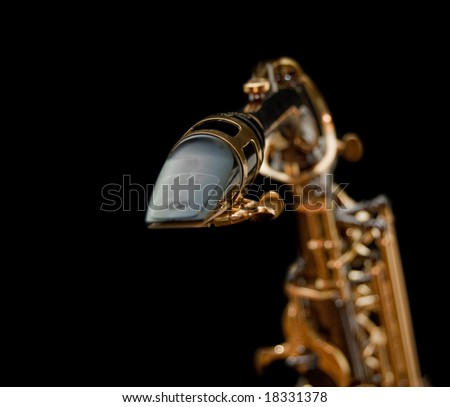 Close-up of a saxophone mouthpiece isolated in black background