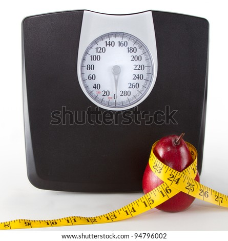Close up of a scale and an apple or pear with a measuring tape on a white background, room for copy-space on scale.