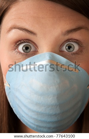 Close-up of a scared woman in a surgical mask