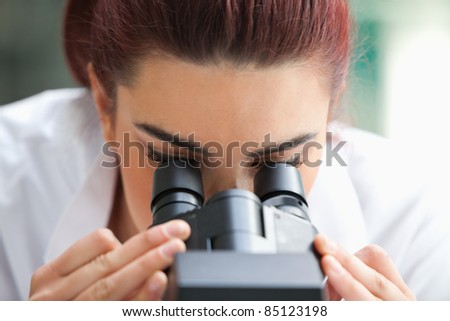 Close up of a scientist looking into a microscope in a laboratory