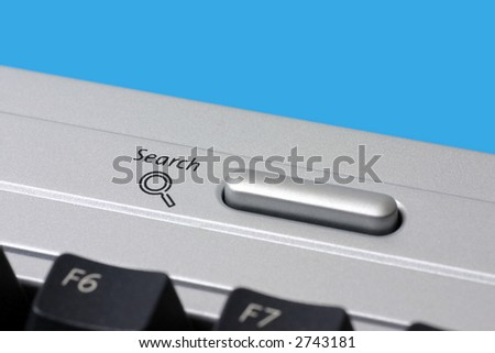 Close-up of a search icon button on a computer keyboard.
