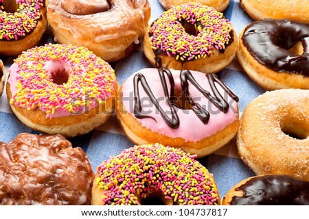 Close up of a selection of colorful donuts.  Focus is on middle row.