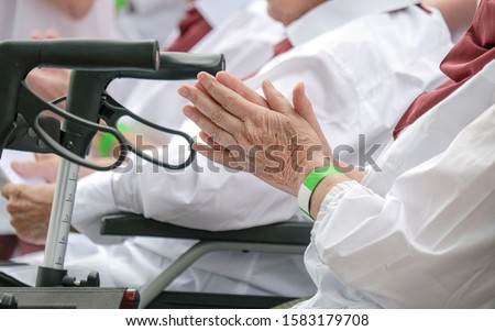 Close-up of a senior woman's hands in the group and walker in the foreground - selective focus