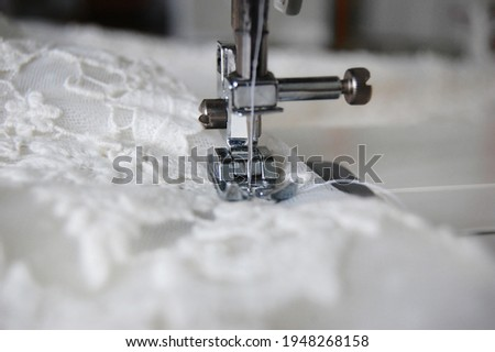 Close up of a sewing machine making alterations of a bride's wedding dress. Foto d'archivio ©