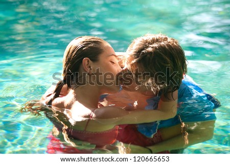 Close up of a sexy young couple submerged in a swimming pool while dressed, hugging and kissing while on a tropical destination vacation.