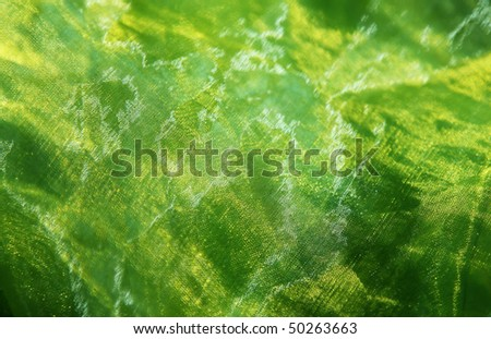 Close-up of a shining organza background in green