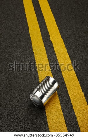 Close up of a shiny metal can sitting on a black asphalt road with yellow stripes.