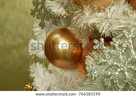 close up of a shiny pink gold ball shaped christmas ornament with blurred silver - Pink And Gold Christmas Decorations