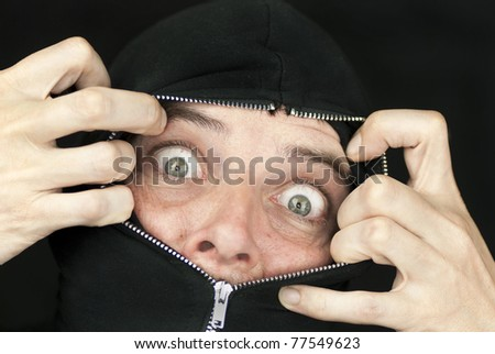Close-up of a shocked man with the hood of his sweatshirt zipped up to his nose trying to break free.