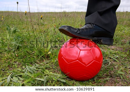 Close-up of a shoe businessman with a red soccer ball, ready to play