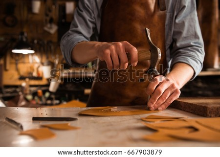 Close up of a shoemaker man working with leather using crafting tools