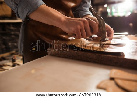 Close up of a shoemaker man working with leather using hammer