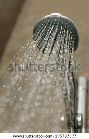 Close up of a shower head flowing water in a bathroom cabin