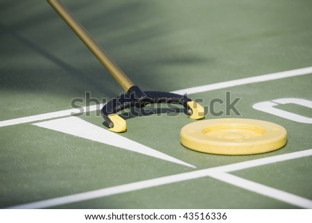 Close-up of a shuffleboard disc and shuffleboard cue
