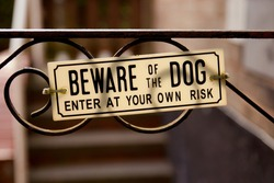Close up of a Sign on a metal gate Beware of the Dog. Enter at your own risk.