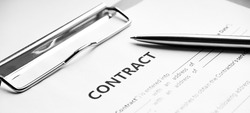 Close-up of a silver pen on docunent contract. Legal contract signing, buy sell real estate contract agreement sign on document paper with black pen