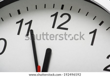 Close up of a simple clock face with the hour and minute hands approaching midnight or twelve o\'clock