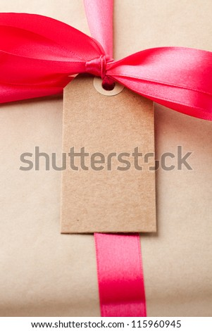 Close-up of a simple gift package with a red ribbon and small card.