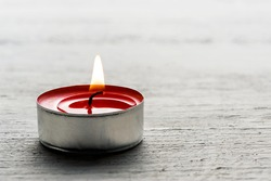 Close up of a single burning red tea light candle in a metal base on a white textured background with copy space for your message or invitation