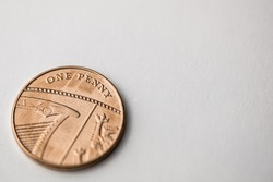 Close up of a single one penny copper coin on a white background shot at an angle.