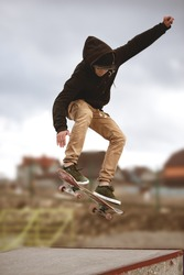 Close up of a skateboarders feet while skating active performance of stunt teenager shot in the air on a skateboard in a skate park
