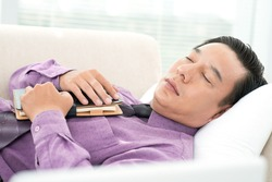 Close-up of a sleeping businessman with notepad in hands