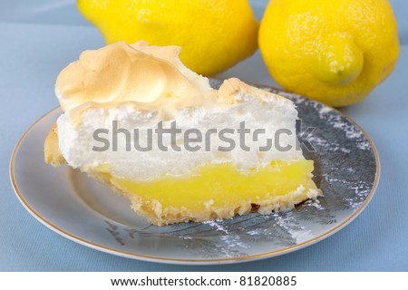 Close up of a slice of homemade lemon meringue pie on an antique plate.