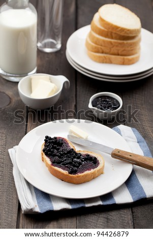 Close-up of a slice of white bread with wild blueberry jam and butter on white plate. Served on a dark rustic wooden table, on a napkin.