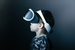 Close-up of a small five-year-old boy playing with virtual reality glasses. 3D gadget technology. VR. XR