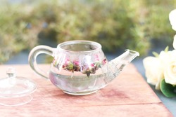 Close-up of a small teapot with rose tea on a wooden stand. Photo in bed colors, a gentle start to the day, a healthy morning drink for women from rosebuds, selective focus.