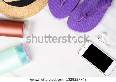 Close-up of a smartphone, flip flops, sunscreen and a hat. Travel concept. Stok fotoğraf ©