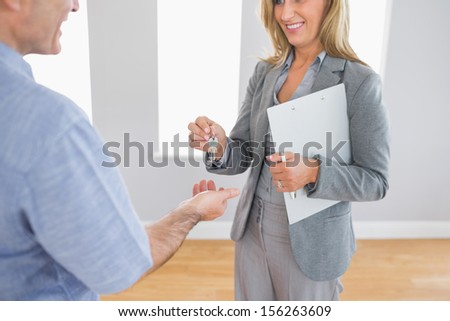 Close up of a smiling blonde realtor delivering a key to a buyer mature customer standing in an empty room