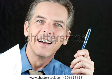Close-up of a smiling businessman offering his pen.