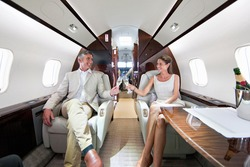 Close up of a smiling couple making a toast with champagne glasses in a private jet