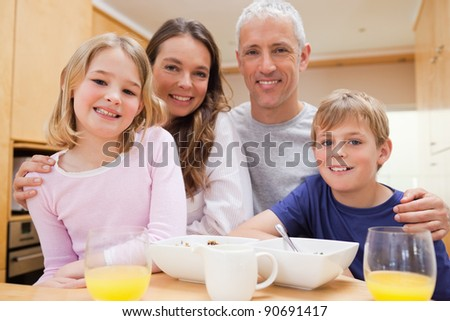 Close up of a smiling family having breakfast in their kitchen