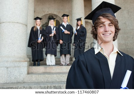 Close-up of a smiling graduate smiling with her friends in background in front of the university
