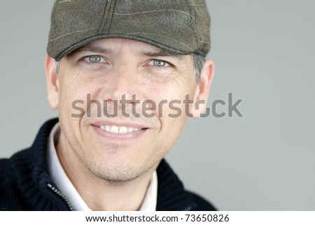 Close-up of a smiling man in a newsboy hat looking to camera.