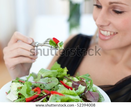 Close-up of a smiling woman eating a salad in the living-room