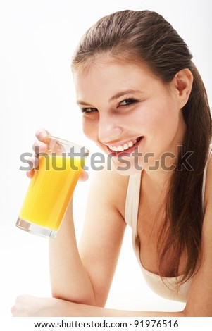 Close up of a smiling woman  with orange juice on foreground - stock photo