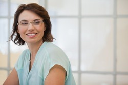 Close-up of a smiling young businesswoman looking away in the office