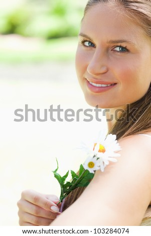 Close up of a smiling young woman with a flower