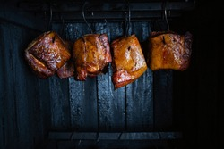 Close up of a smoked meat and belly or beech meat with dark crust in the smokehouse or smoker, food concept