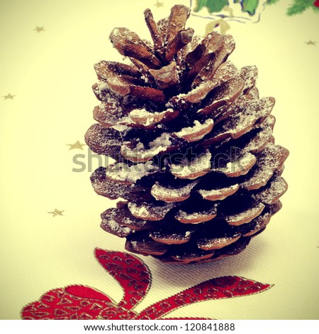 close up of a snowy pine cone on a christmas patterned tablecloth, with a retro effect