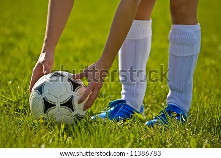 Close up of a soccer ball with hands and feet